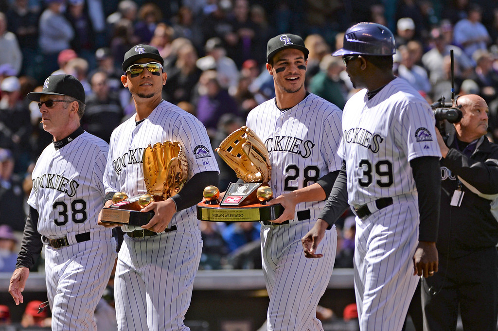 . (From left) Coach Rene Lachemann, Carlos Gonzalez, Nolan Arenado and coach Stu Cole walk off the field after opening ceremonies.  (Photo by Hyoung Chang/The Denver Post)