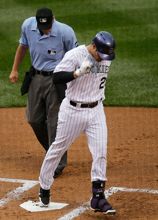. Colorado Rockies\' Nolan Arenado celebrates as he crosses home plate after hitting a solo home run off Cincinnati Reds starting pitcher Johnny Cueto during the second inning of a baseball game on Friday, Aug. 15, 2014, in Denver. (AP Photo/Jack Dempsey)