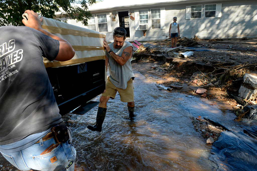 ". Scott Koester gets help from his nephew Kyron Brady, left, while  carrying belongings from their home in Lyons,  CO September 20, 2013. Koester expects that the home will be condemned afte the recent flooding. Koester expects that the home will be condemned after the recent flooding. He said, ""we\'ve been here 10 years now and it\'s all gone. I don\'t know how you\'d save this house.\""  Friday was the second day residents were allowed to return to their homes.  (Photo By Craig F. Walker / The Denver Post)"