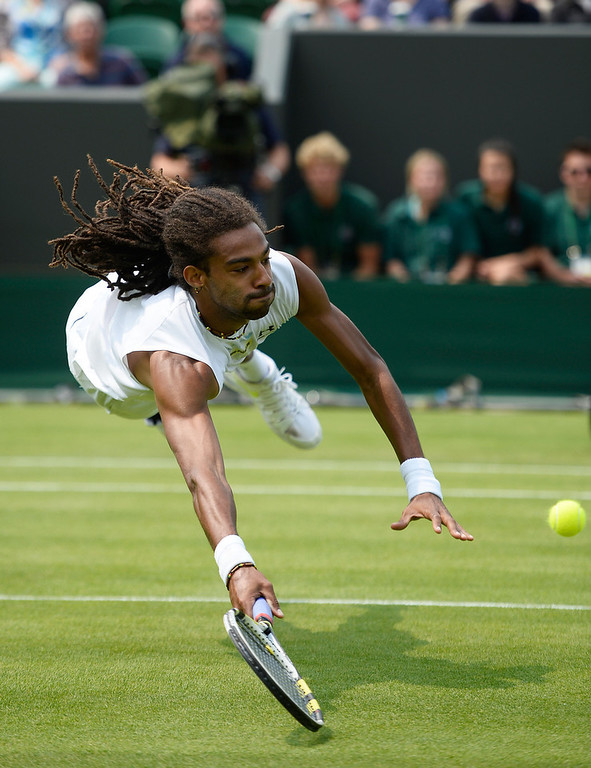 . Dustin Brown of Germany dives to return a shot during his Gentlemen\'s Singles second round match against Lleyton Hewitt of Australia on day three of the Wimbledon Lawn Tennis Championships at the All England Lawn Tennis and Croquet Club on June 26, 2013 in London, England.  (Photo by Dennis Grombkowski/Getty Images)