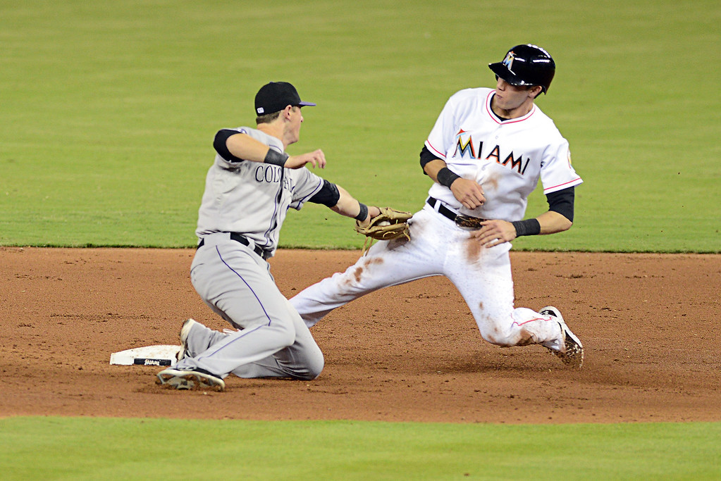 . MIAMI, FL - AUGUST 24:  Christian Yelich #21 of the Miami Marlins gets by DJ LeMahieu #9 of the Colorado Rockies at Marlins Park on August 24, 2013 in Miami, Florida.  (Photo by Jason Arnold/Getty Images)