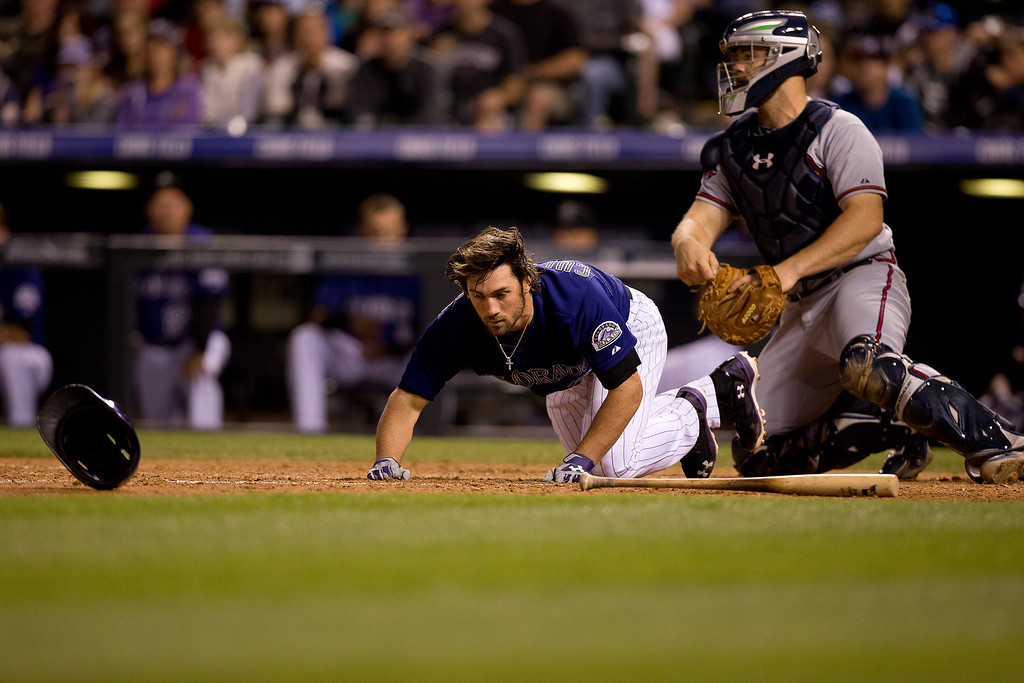 . Charlie Culberson #23 of the Colorado Rockies loses his helmet during an at-bat in the ninth inning as catcher Evan Gattis #24 of the Atlanta Braves looks on at Coors Field on June 9, 2014 in Denver, Colorado.  (Photo by Justin Edmonds/Getty Images)