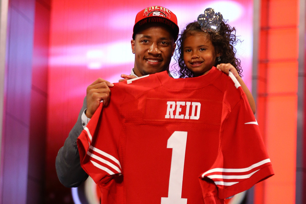 . Eric Reid of the LSU Tigers holds his daughter Eric Reid of the LSU Tigers as they hold up a jersey on stage after he was picked #18 overall by the San Francisco 49ers in the first round of the 2013 NFL Draft at Radio City Music Hall on April 25, 2013 in New York City.  (Photo by Al Bello/Getty Images)