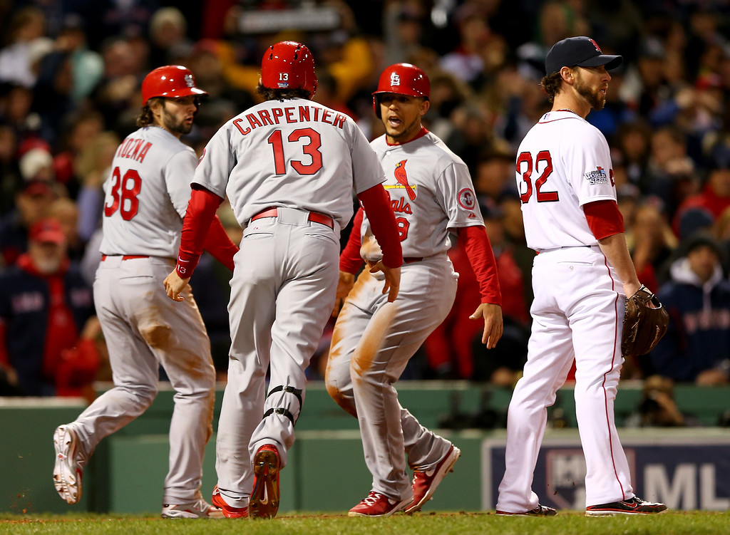 . BOSTON, MA - OCTOBER 24:  Matt Carpenter #13 celebrates with Carlos Beltran #3 and Pete Kozma #38 of the St. Louis Cardinals after three runs scored in the seventh inning against the Boston Red Sox during Game Two of the 2013 World Series at Fenway Park on October 24, 2013 in Boston, Massachusetts.  (Photo by Elsa/Getty Images)