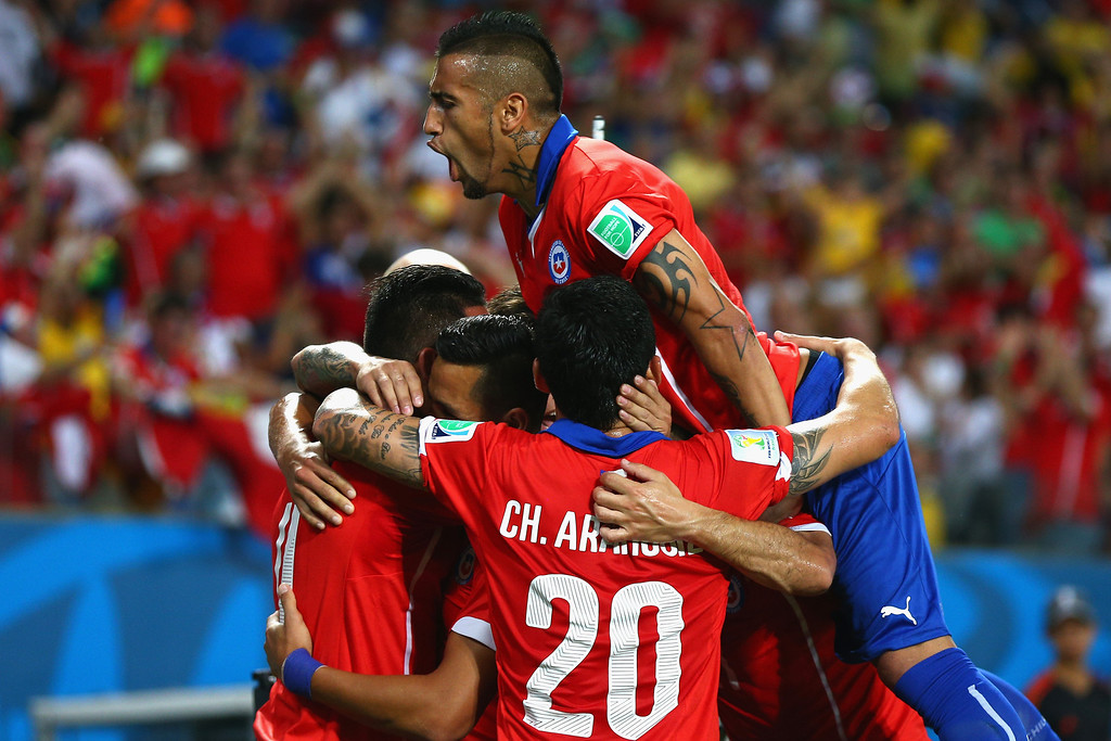 . Arturo Vidal of Chile jumps on a group of teammates celebrating their first goal by Alexis Sanchez (C) during the 2014 FIFA World Cup Brazil Group B match between Chile and Australia at Arena Pantanal on June 13, 2014 in Cuiaba, Brazil.  (Photo by Cameron Spencer/Getty Images)