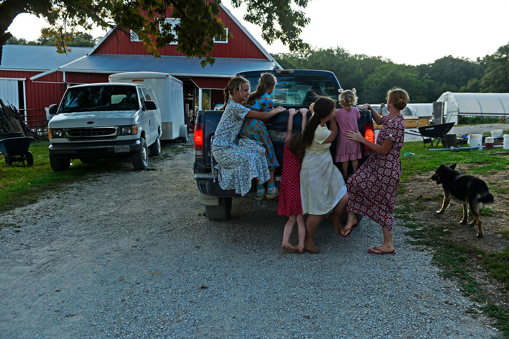 . As Gerry Newman returns home six of his daughters hold onto the back of his truck for a ride down the driveway at their family farm in Trenton, Mo., Wednesday, September 25, 2013. During this trip into town, which is about three miles form the farm, their father bought them all gardening shovels to use when they plant strawberries. (Photo By RJ Sangosti/The Denver Post)