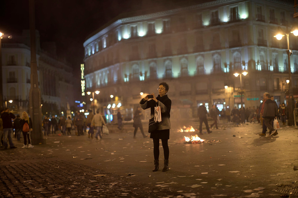 . A woman takes a snapshot after a demonstration against layoffs of street cleaners and garbage collectors in Madrid, Spain, Monday, Nov. 4, 2013. Trash collectors in Madrid have started bonfires and set off firecrackers during a noisy protest in one of the Spanish capitalís main squares as they prepare to start an open-ended strike. Hundreds of street cleaners and garbage collectors who work in the cityís public parks converged on the Puerta del Sol plaza late Monday. (AP Photo/Daniel Ochoa de Olza)