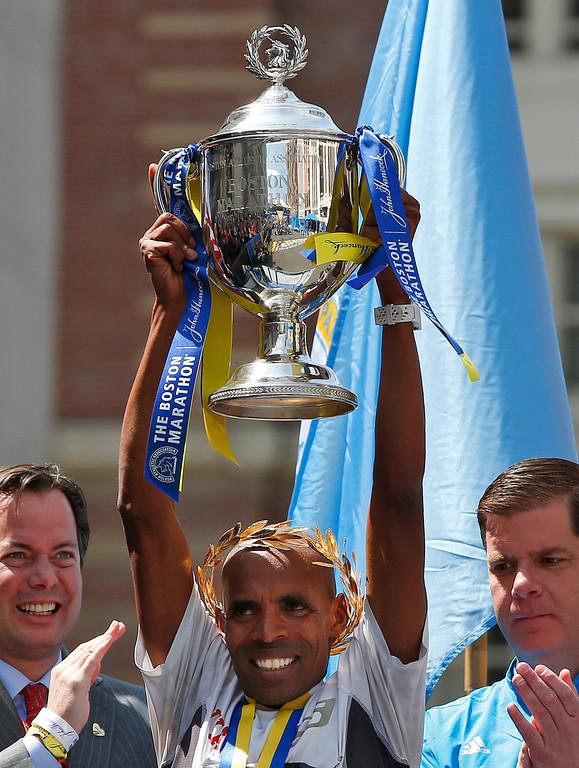 . Meb Keflezighi, of San Diego, Calif., hoists his trophy after winning the 118th Boston Marathon Monday, April 21, 2014 in Boston. (AP Photo/Elise Amendola)