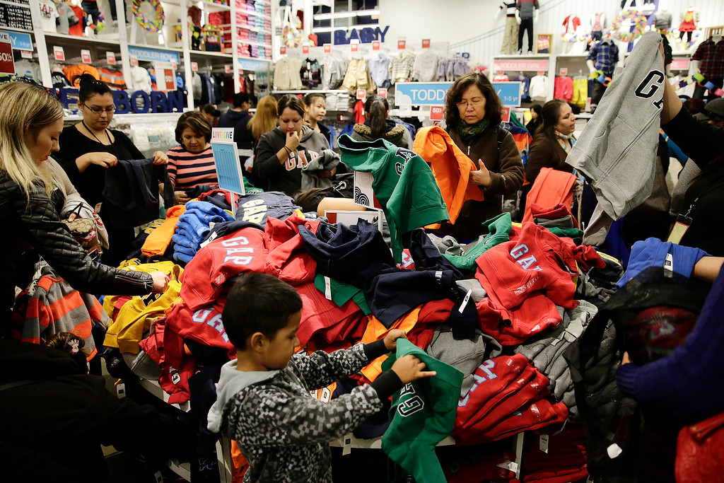. People shop at a Gap factory store at the Citadel Outlets on Thursday, Nov. 28, 2013, in Los Angeles . Instead of waiting for Black Friday, which is typically the year\'s biggest shopping day, more than a dozen major retailers are opening on Thanksgiving day this year. (AP Photo/Jae C. Hong)