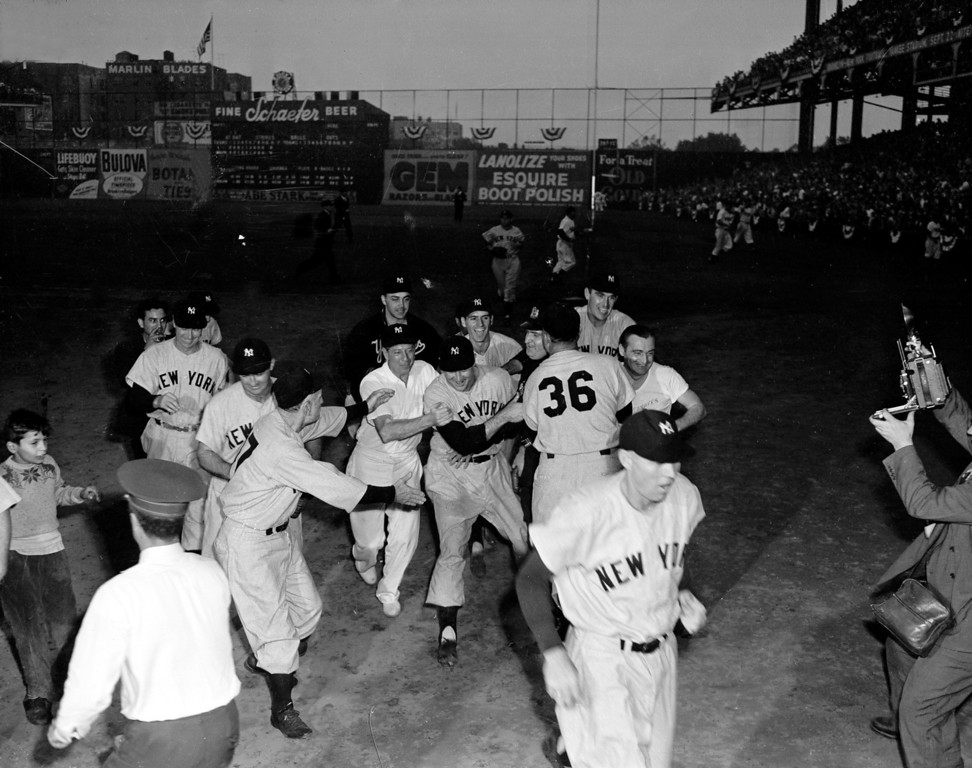 . New York Yankees manager Casey Stengel, second from left, foreground, reaches out to congratulate relief pitcher Joe Page, center, while fellow Yankees mob the lefthander after the final out, in the World Series with the Brooklyn Dodgers at Ebbets Field, Brooklyn, New York, October 9, 1949.  The Yankees capture the 12th championship with a 10 to 6 victory in game five. Left to right are: Yankees coach Jim Turner; Billy Johnson; Stengel; a clubhouse attendant; Clarence Marshall (behind attendant); Page; Gerry Coleman (behind Page); Johhny Mize (36);  Johnny Lindell (behind Mize); and a clubhouse attendant. In foreground right is coach Bill Dickey. (AP Photo)