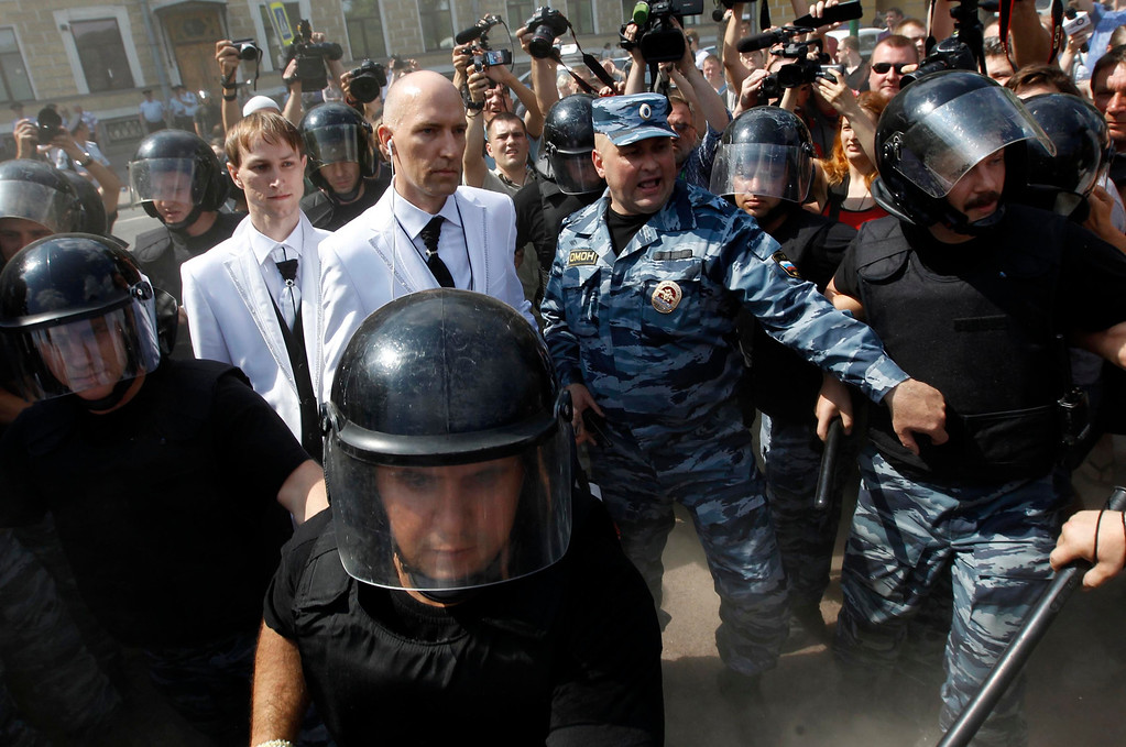 . Russian same-sex couple Yury Gavrikov (R) and Maxim Lysak, surrounded by the riot police officers, arrive at a Gay Pride event in St. Petersburg, June 29, 2013. Dozens of gay and lesbian rights activists and their supporters gathered for the event but were attacked by anti-gay protesters and later dispersed by the police.  REUTERS/Alexander Demianchuk