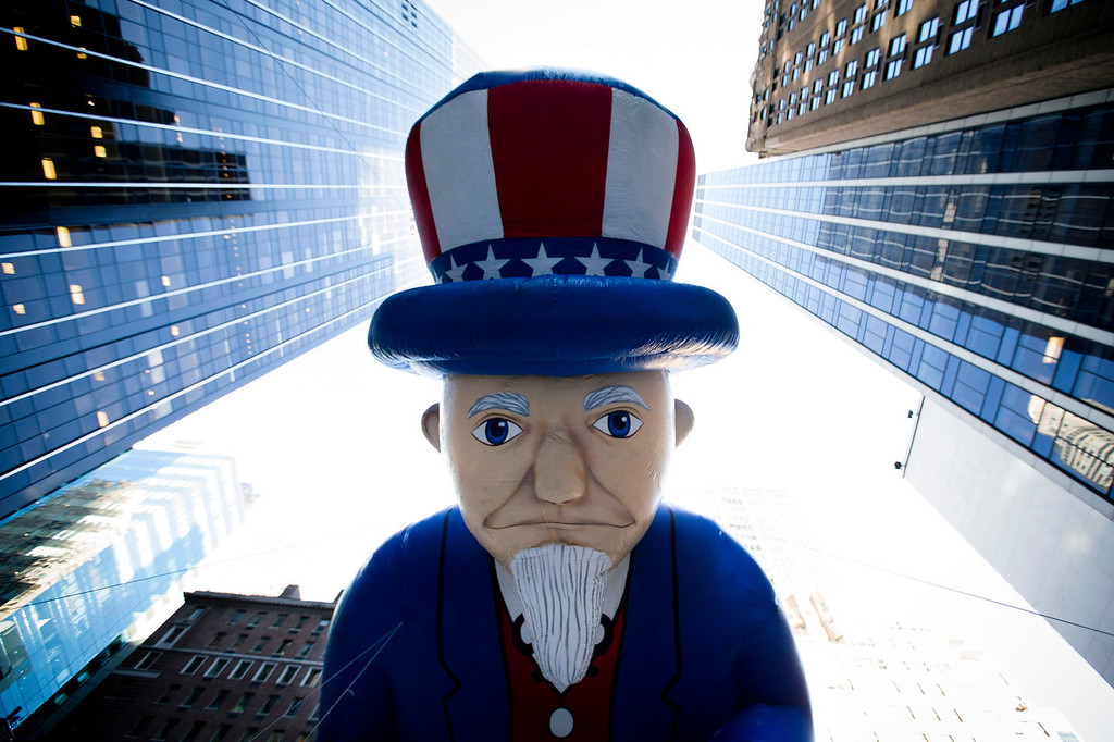 . A giant Uncle Sam balloon is marched down 6th Avenue during the 87th Annual Macy\'s Thanksgiving Day Parade, Thursday, Nov. 28, 2013, in New York. After fears the balloons could be grounded if sustained winds exceeded 23 mph, Snoopy, Spider-Man and the rest of the iconic balloons received the all-clear from the New York Police Department to fly between Manhattan skyscrapers on Thursday. (AP Photo/John Minchillo)