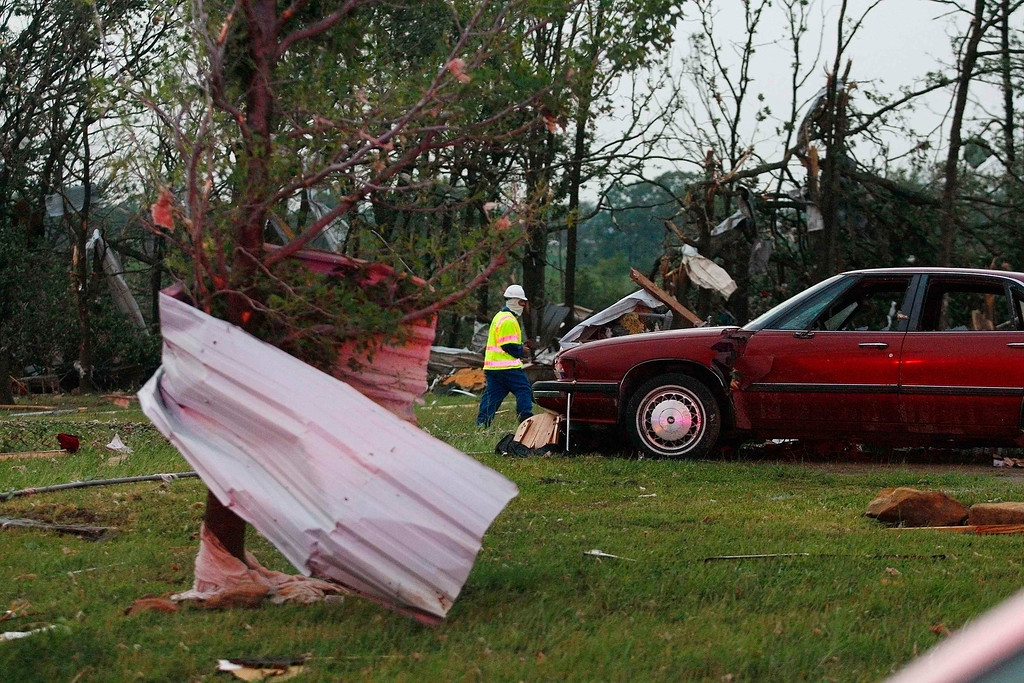 . An official walks next to storm debris at a mobile home park which was destroyed by a tornado on Sunday, west of Shawnee, Oklahoma May 19, 2013. A tornado half a mile wide struck near Oklahoma City on Sunday, part of a massive storm front that hammered the central United States. News reports said at least one person had died. REUTERS/Bill Waugh