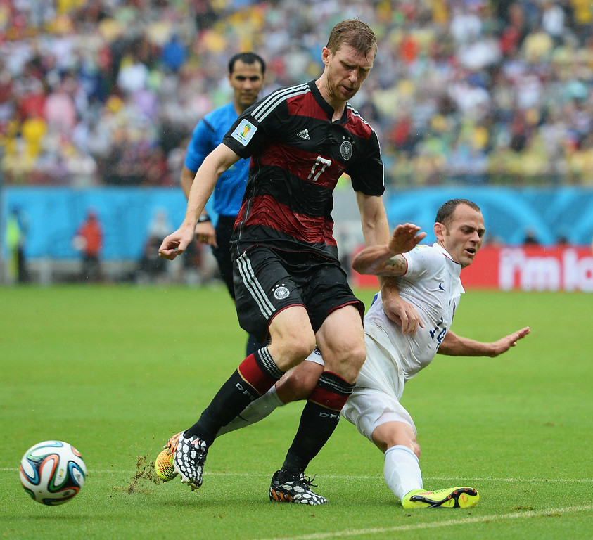 . Per Mertesacker of Germany and Brad Davis of the United States compete for the ball during the 2014 FIFA World Cup Brazil group G match between the United States and Germany at Arena Pernambuco on June 26, 2014 in Recife, Brazil.  (Photo by Jamie McDonald/Getty Images)