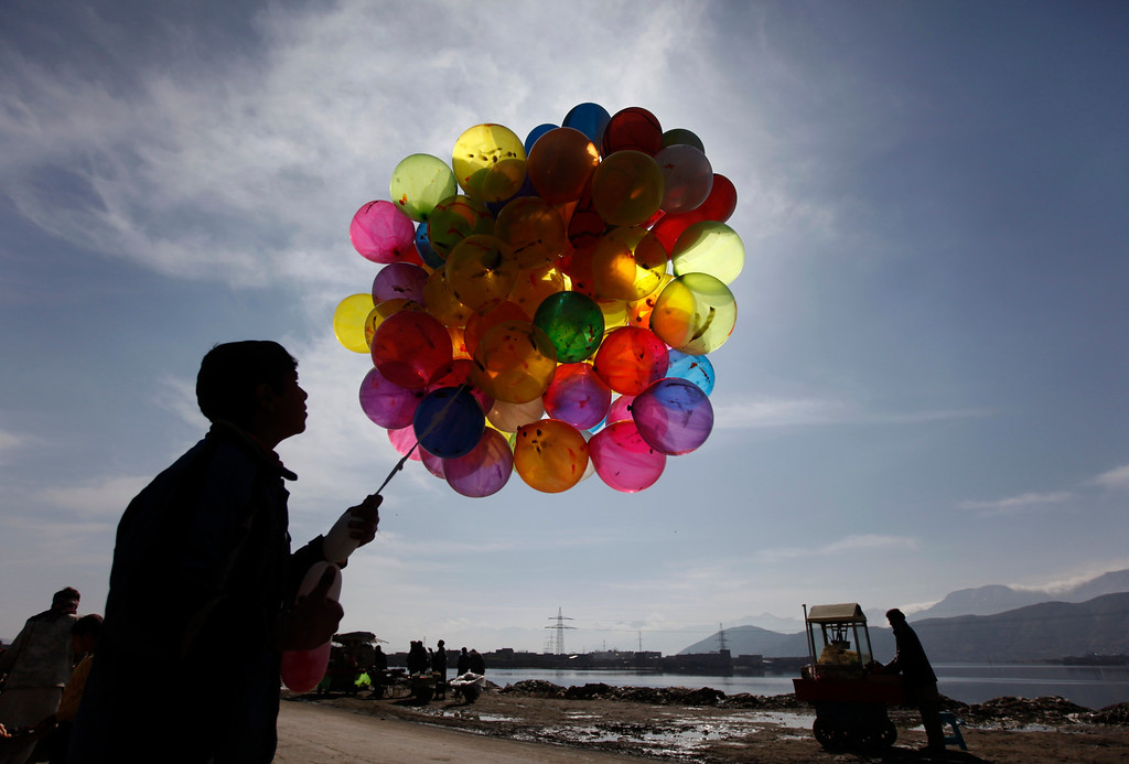 . An Afghan boy sells balloons during a gathering to celebrate the Afghan New Year (Nawroz) in Kabul March 21, 2013. Nawroz, also known as Persian New Year, is observed during the March equinox, marking the first day of spring.  REUTERS/Mohammad Ismail