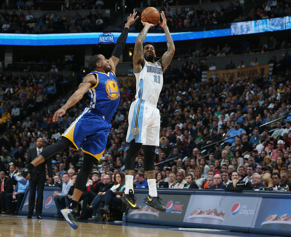 . Golden State Warriors guard Andre Iguodala, left, tries to block shot by Denver Nuggets forward Wilson Chandler in the fourth quarter of the Warriors\' 89-81 victory in an NBA basketball game in Denver on Monday, Dec. 23, 2013. (AP Photo/David Zalubowski)