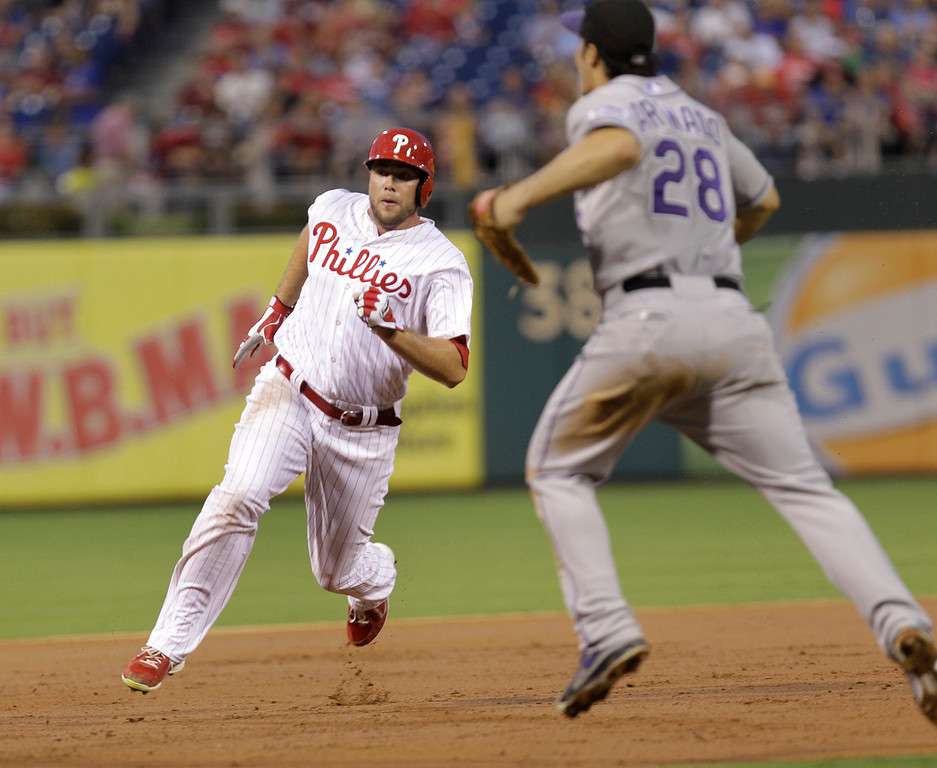 . Philadelphia Phillies\' Darin Ruf advances to third on a double by John Mayberry Jr. as Colorado Rockies third baseman Nolan Arenado looks to the outfield in the second inning in a baseball game, Wednesday, Aug. 21, 2013, in Philadelphia. (AP Photo/Laurence Kesterson)