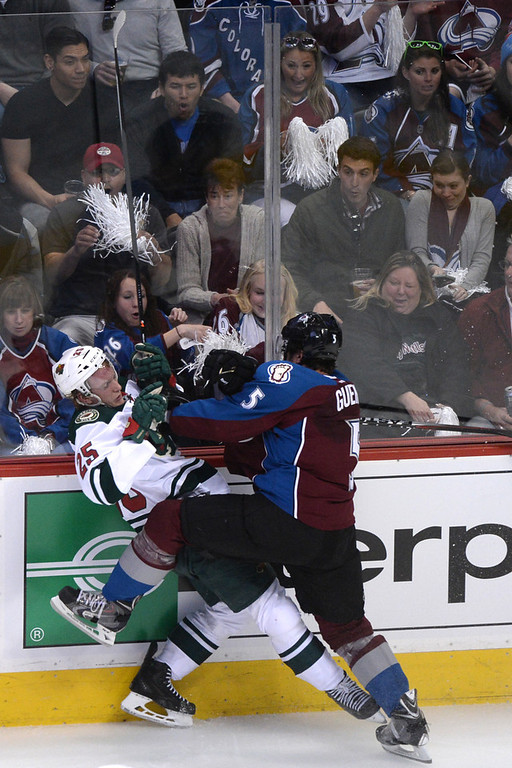 . Nate Guenin (5) of the Colorado Avalanche checks Jonas Brodin (25) of the Minnesota Wild during the first period of action. The Colorado Avalanche hosted the Minnesota Wild in the first round of the NHL playoffs at the Pepsi Center on Thursday, April 17, 2014. (Photo by Karl Gehring/The Denver Post)