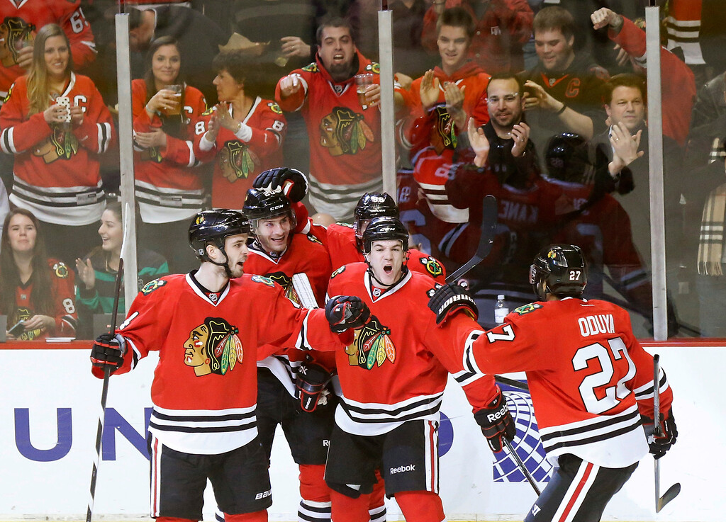 . Chicago Blackhawks defenseman Johnny Oduya celebrates his goal with teammates from left, Niklas Hjalmarsson (4) Brandon Saad, Andrew Shaw, and Patrick Kane behind Shaw, during the second period of an NHL hockey game against the Colorado Avalanche, Tuesday, Jan. 14, 2014, in Chicago. (AP Photo/Charles Rex Arbogast)
