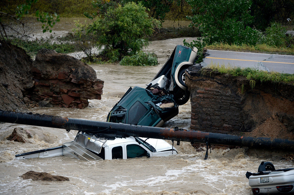 ". ADDS MORE PRECISE LOCATION INFORMATION- Three vehicles sit in water after crashing where a road collapsed following flooding at Highway 287 and Dillon at the Broomfield/Lafayette border, Colo., on Thursday, Sept. 12, 2013. Three people were rescued. The National Weather Service has warned of an ""extremely dangerous and life-threatening situation\"" throughout the region. (AP Photo/The Denver Post, Andy Cross)"
