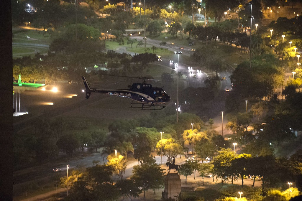 """. A police helicopter patrols during clashes with demonstrators after a protest for the \""""Teachers\' day\"""", on October 15, 2013 in Rio de Janeiro, Brazil.  AFP PHOTO/VANDERLEI ALMEIDA/AFP/Getty Images"""