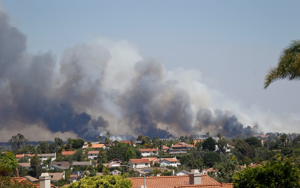 . In this view looking north from Encinitas, Calif, smoke rises from a wild fire Wednesday, May 14, 2014, in Carlsbad. (AP Photo)
