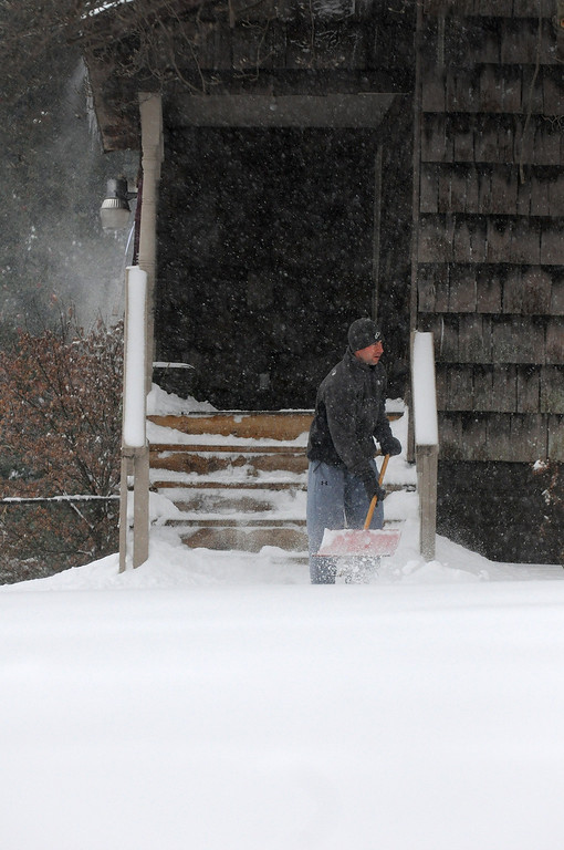 . Matt Wadiak shovels a path on his steps after heavy snowfall moved through the region on Friday, Dec. 6, 2013, in Carbondale, Ill. (AP Photo/The Southern Illinoisan, Steve Matzker)