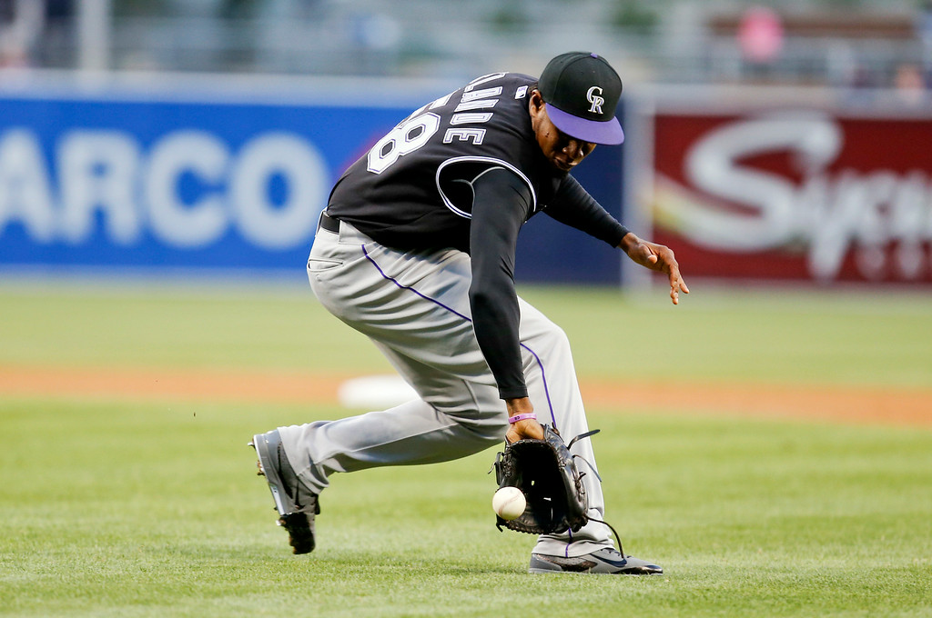 . Colorado Rockies starting pitcher Yohan Flande backhands a slow roller hit by San Diego Padres\' Yangervis Solarte in the first inning of a baseball game Tuesday, Aug. 12, 2014, in San Diego. Flande got the out at first. (AP Photo/Lenny Ignelzi)