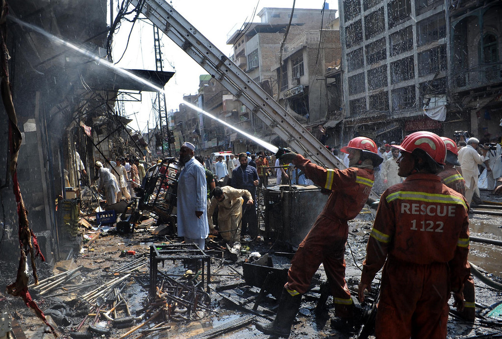 . Pakistani firefighters extinguish a fire after a bomb explosion in the busy Kissa Khwani market in Peshawar on September 29, 2013.  AFP PHOTO /  A. MAJEED/AFP/Getty Images