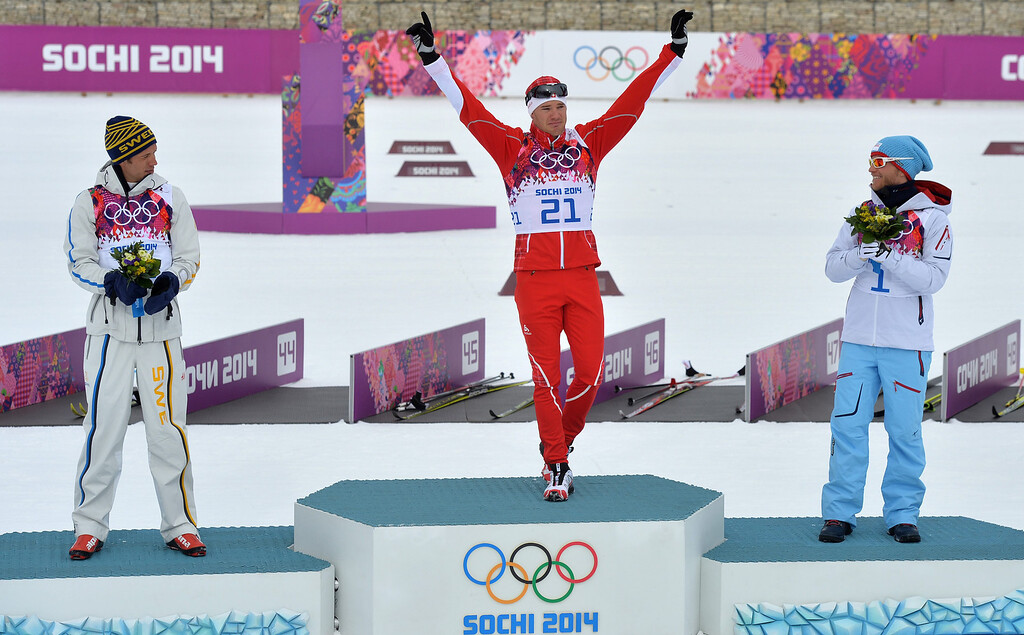 . Dario Cologna of Switzerland (C) celebrates during the flower ceremony with second placed Marcus Hellner of Sweden (L) and third placed Martin Johnsrud Sundby of Norway after the Men\'s 15km + 15km Skiathlon competition in the Laura Cross Country Center at the Sochi 2014 Olympic Games, Krasnaya Polyana, Russia, 09 February 2014.  EPA/HENDRIK SCHMIDT