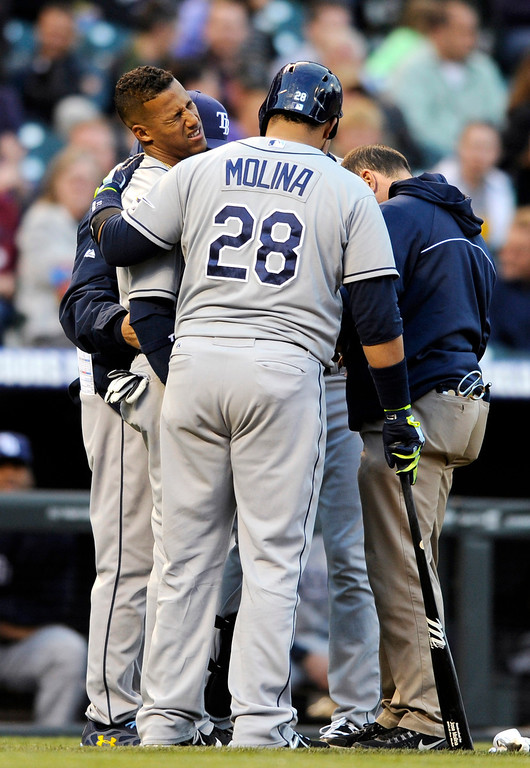 . Tampa Bay Rays\' Yunel Escobar grimaces as trainers and Jose Molina check on Escobar, who was hit by a pitch from Colorado Rockies starter Jon Garland during the second inning of a baseball game on Saturday, May 4, 2013, in Denver. Escobar left the game. (AP Photo/Jack Dempsey)