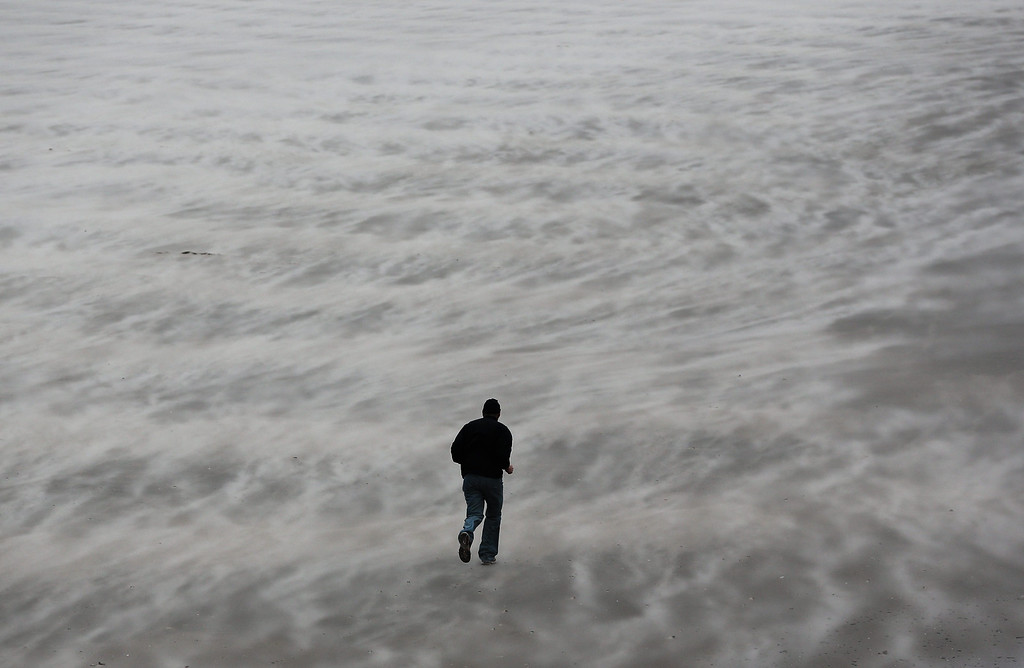 . A man runs through sand blown up by the wind at the North Sea beach in Blankenberge, Belgium, 05 December 2013. Storm front \'Xaver\' will hit the Belgian North Sea with heavy gusts and a wind velocity of more than 100 kilometers per hour on 05 December.  EPA/JULIEN WARNAND