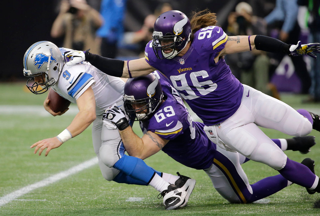 . Detroit Lions quarterback Matthew Stafford, left, is sacked by Minnesota Vikings defenders Jared Allen (69) and Brian Robison (96) during the first half of an NFL football game, Sunday, Dec. 29, 2013, in Minneapolis. (AP Photo/Ann Heisenfelt)
