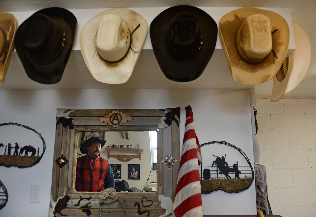 . KERSEY, CO - JANUARY 8, 2014: Rancher Jon Flack looks over his collection of cowboy hats in his office on his ranch in Kersey, Co on January 8, 2014.   He is one of many ranchers that hasn\'t gotten much help from the government in helping to pay for expenses on his ranch incurred from the September floods. His losses included about  200 bales of hay worth about $30,000 which were destroyed when they were fully submerged in water.    As well many fences, fencing, corrals, ditches and land were severely damaged from the floods and need to be repaired. He has also had to rent pasture land to keep his cattle on because his land was too saturated for them to graze on.   (Photo By Helen H. Richardson/ The Denver Post)