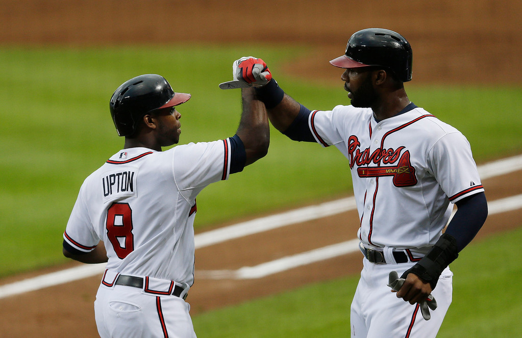 . Atlanta Braves left fielder Justin Upton (8) celebrates with teammate Jason Heyward after hitting a two-run home run in the first inning of a baseball game against the Colorado Rockies in Atlanta,   Thursday, Aug. 1, 2013. (AP Photo/John Bazemore)