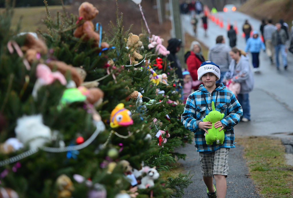 . A young boy decorates Christmas trees set up at a makeshift shrine to the victims of a elementary school shooting in Newtown, Connecticut, December 16, 2012.  A young gunman slaughtered 20 small children and six teachers on December 14,2012 after walking into a school in an idyllic Connecticut town wielding at least two sophisticated firearms. EMMANUEL DUNAND/AFP/Getty Images