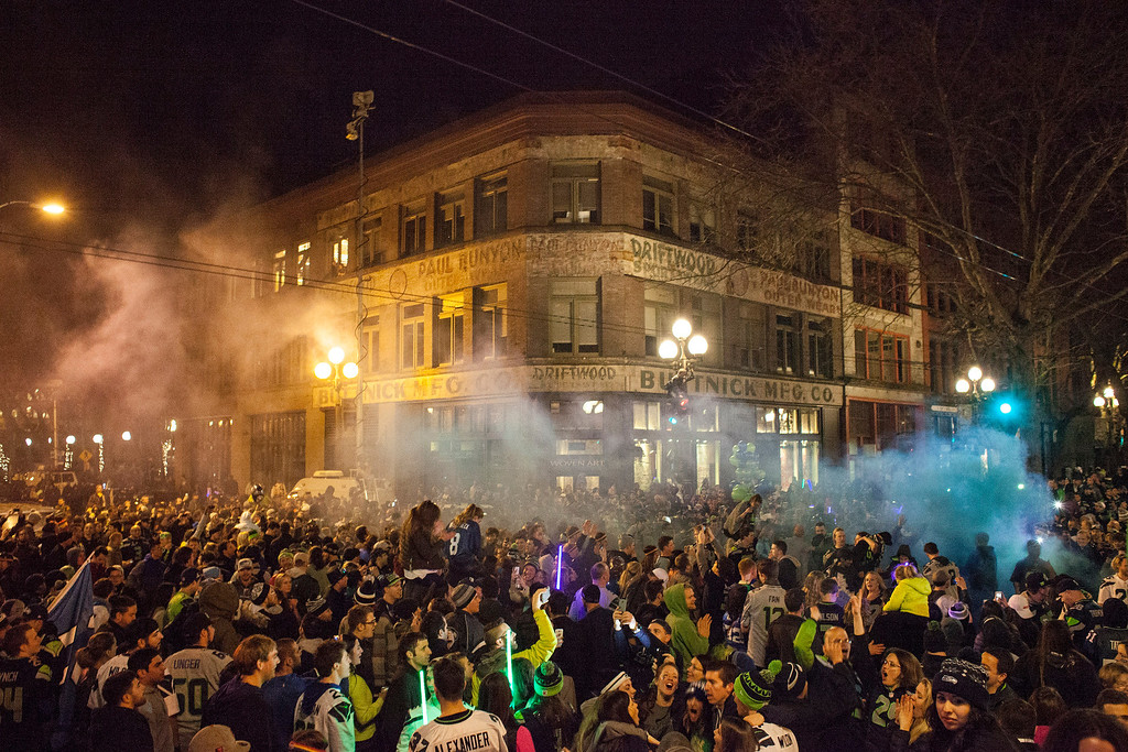 . Seattle Seahawks fans celebrate in the middle of 1st Avenue on February 2, 2014 in Seattle, Washington. Hundreds of people flooded the streets of downtown Seattle after the Seahawks defeated the Denver Broncos in the Super Bowl.  (Photo by David Ryder/Getty Images)