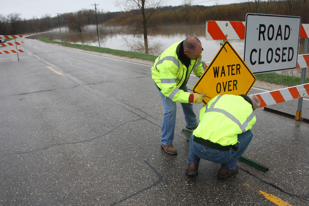 . Des Moines County workers, Trevor Williams, left, and Tom Watznauer, block off Highway 99 at 115th St. north of the Burlington Municipal Waterworks plant as water from Flint Creek flows over the roadway Thursday April 18, 2013 in Burlington, Iowa.(AP Photo/The Hawk Eye, John Gaines)