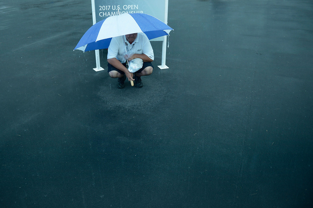 . A man huddles under an umbrella after play was suspended during a storm at the first round the US Open at Merion Golf Club June 13, 2013 in Ardmore, Pennsylvania. AFP PHOTO/Brendan  SMIALOWSKI/AFP/Getty Images