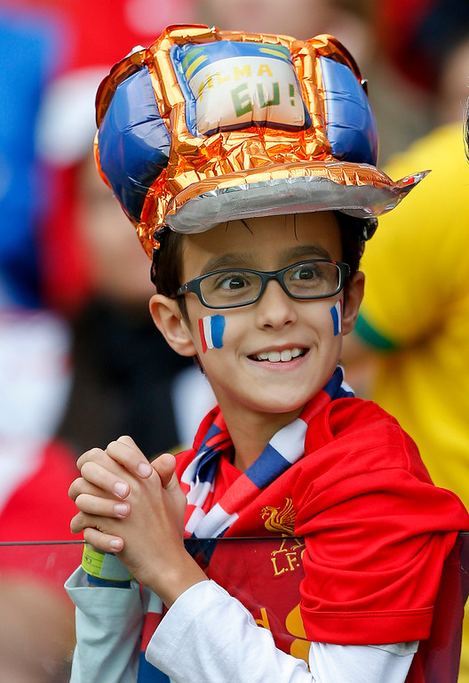 . A young supporter waits for the start go the group E World Cup soccer match between France and Honduras at the Estadio Beira-Rio in Porto Alegre, Brazil, Sunday, June 15, 2014. (AP Photo/Jon Super)