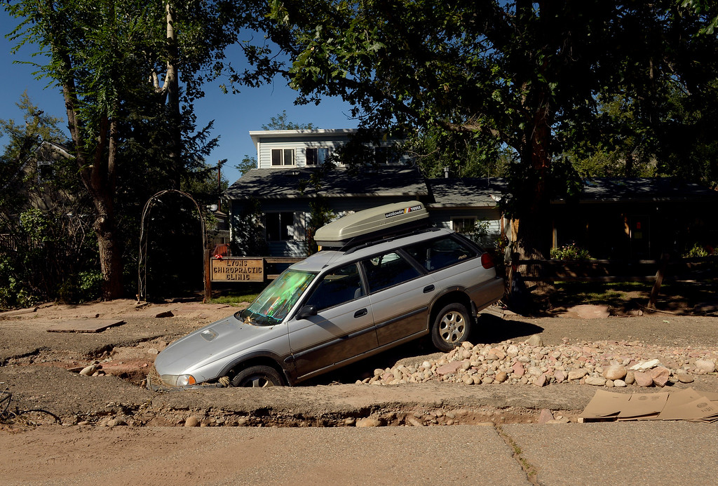 . A car rests in a sinkhole in Lyons,  CO September 20, 2013. Friday was the second day residents were allowed to return to their homes.  (Photo By Craig F. Walker / The Denver Post)