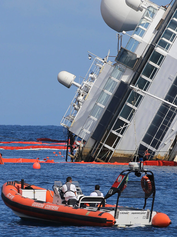 . A dark line, marking a previously submerged part, gives evidence of the movement of the Costa Concordia ship, lying on its side on the Tuscan Island of Giglio, Italy, Monday, Sept. 16, 2013. An international team of engineers is trying a never-before attempted strategy to set upright the luxury liner, which capsized after striking a reef in 2012 killing 32 people. (AP Photo/Andrea Sinibaldi, Lapresse)