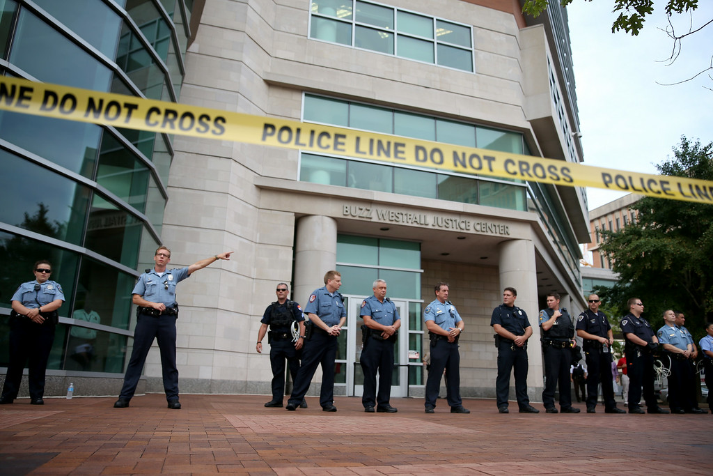 . CLAYTON, MO - AUGUST 20: Police stand guard outside the entrance as demonstrators protest outside of the Buzz Westfall Justice Center where a grand jury will begin looking at the circumstances surrounding the fatal police shooting of an unarmed teenager Michael Brown on August 20, 2014 in Clayton, Missouri. Brown was shot and killed by a Ferguson, Missouri police officer on August 9. Despite the Brown family\'s continued call for peaceful demonstrations, violent protests have erupted nearly every night in Ferguson since his death  (Photo by Joe Raedle/Getty Images)
