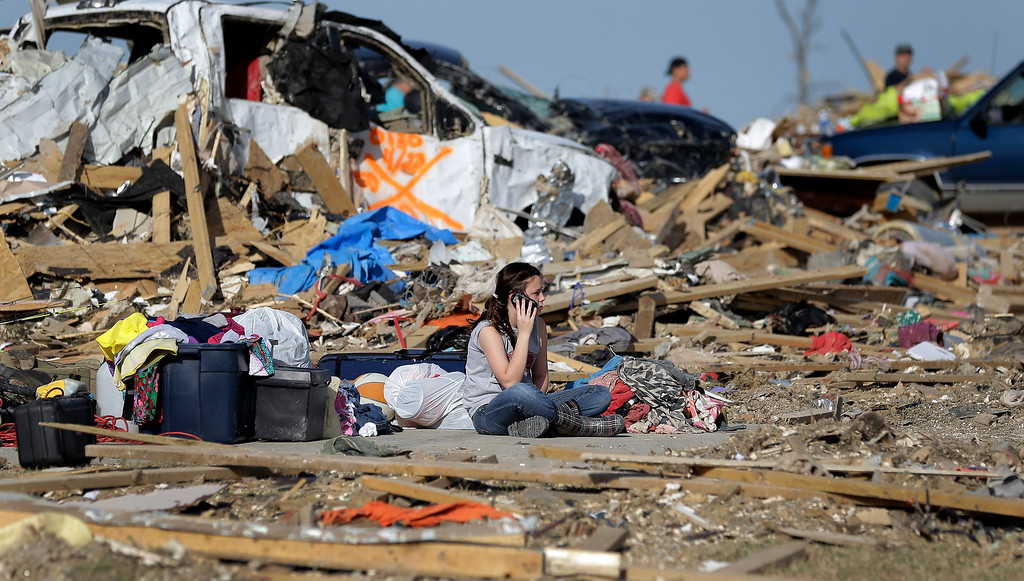 . Destiny Simmons sits in the rubble of her home that was destroyed by a tornado as she talks on a cell phone, Monday, April 28, 2014, in Vilonia, Ark. (AP Photo/Eric Gay)
