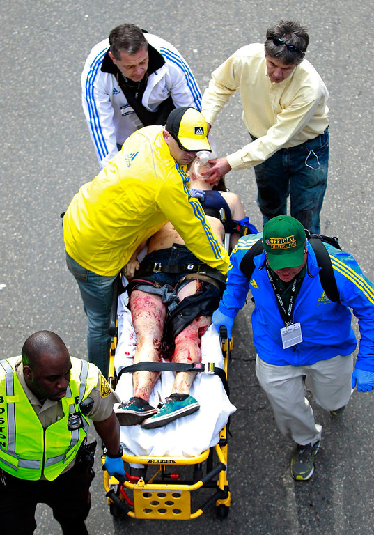 . Medical workers aid an injured man at the finish line of the 2013 Boston Marathon following an explosion in Boston, Monday, April 15, 2013. Two bombs exploded near the finish of the Boston Marathon on Monday, killing two people, injuring 22 others and sending authorities rushing to aid wounded spectators, race organizers and police said. (AP Photo/Charles Krupa)