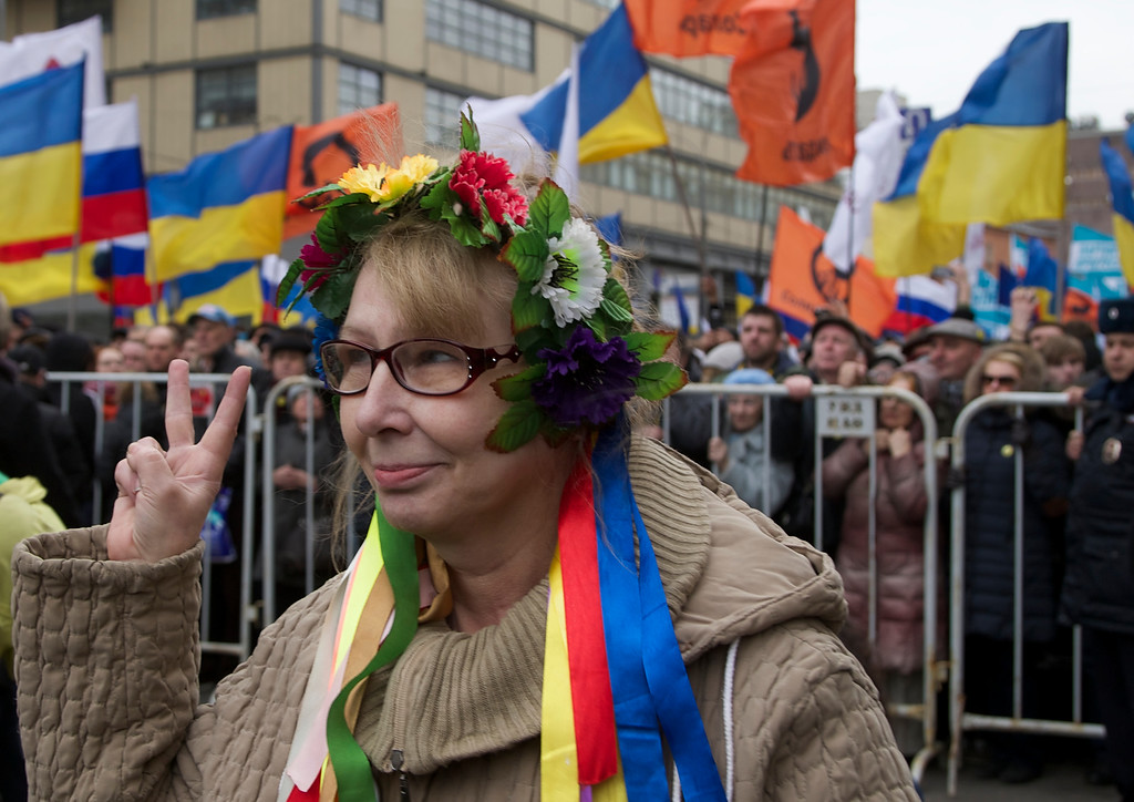 . An woman dressed in a Ukrainian folk costume shows V-sing as demonstrators hold Russian and Ukrainian flags during a massive rally to oppose  president Vladimir Putin\'s policies in Ukraine, in Moscow, Saturday, March 15, 2014. Large rival marches have taken place in Moscow over Kremlin-backed plans for Ukraineís province of Crimea to break away and merge with Russia. More than 10,000 people turned out Saturday for a rally in the center of the city held to oppose what many demonstrators described as Russia\'s invasion of the Crimean Peninsula. In a nearby location, a similar sized crowd voiced its support for Crimea\'s ethnic Russian majority, who Moscow insists is at threat from an aggressively nationalist leadership now running Ukraine. (AP Photo/Alexander Zemlianichenko)