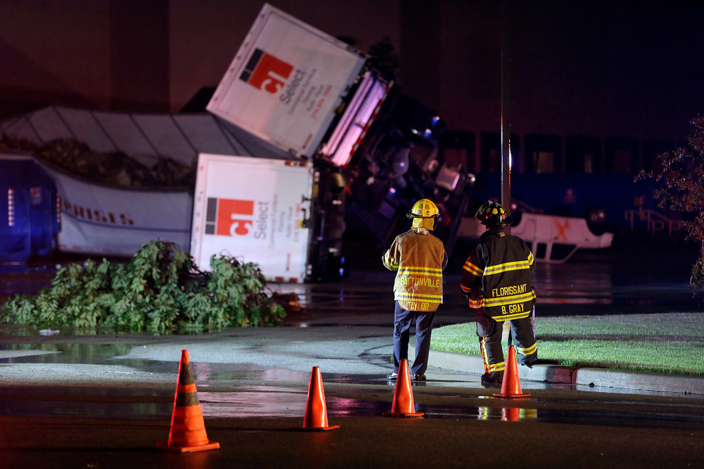 . Rescue personnel stand near overturned trucks in an industrial park after strong storms moved through the area Friday, May 31, 2013, in St. Louis. (AP Photo/Jeff Roberson)