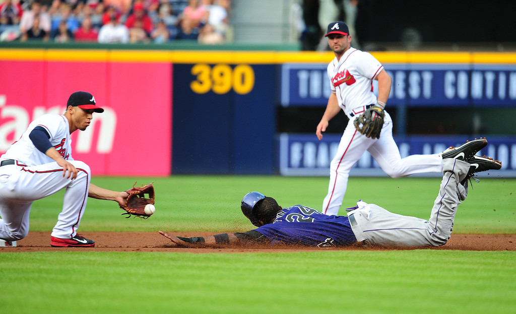 . Dexter Fowler #24 of the Colorado Rockies is tagged out on a steal attempt by Dan Uggla #26 of the Atlanta Braves at Turner Field on July 31, 2013 in Atlanta, Georgia. (Photo by Scott Cunningham/Getty Images)
