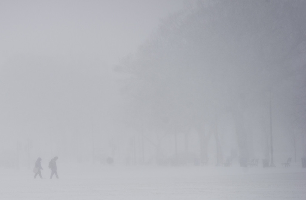 . People walk on the National Mall in Washington, DC, January 21, 2014, as snow falls during a storm.  AFP PHOTO / Saul LOEB/AFP/Getty Images