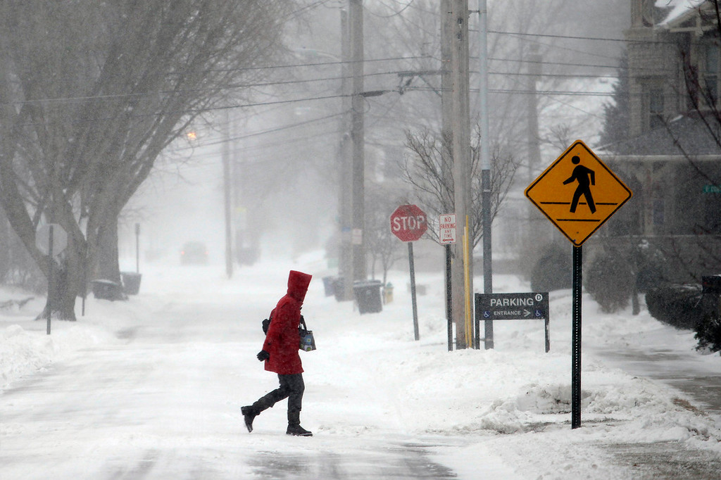 . A woman crosses North Summit Street, Thursday, Jan. 2, 2014, on her way to the Wood County Courthouse in Bowling Green, Ohio. A winter weather advisory is in effect for the area. (AP Photo/Sentinel-Tribune, J.D. Pooley)